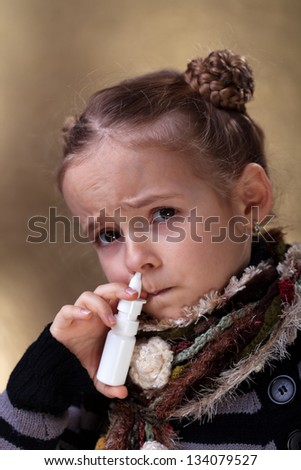 Young girl using nasal spray looking worried