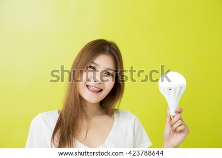 Young girl using save energy lamp on green background
