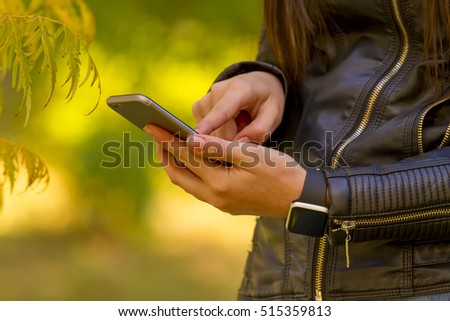Young girl using smart phone in the park, wears smart watch in everyday lifestyle. Focus on smart phone!