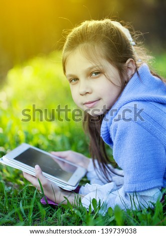 Young girl using tablet outdoor laying on grass