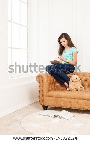 Young girl using tablet while sitting on couch at home - stock photo