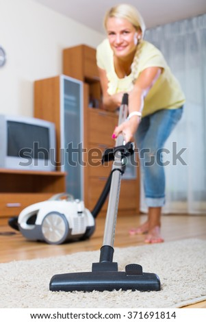 Young girl using vacuum cleaner during regular clean-up - stock photo