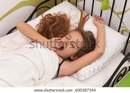 Young girl waking up in her bed - stretching and yawning