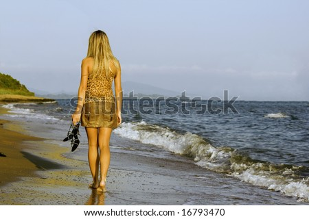 Young girl walking evening barefooted on the sea coast - stock photo