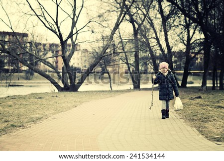 Young girl walking in the autumn scenery.