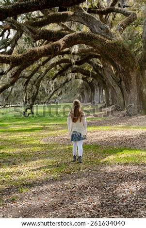 Young girl walking in the park, beautiful oak trees in the background. - stock photo