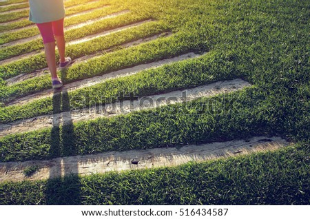 Young girl walking outdors on a trail over green grass at sunset
