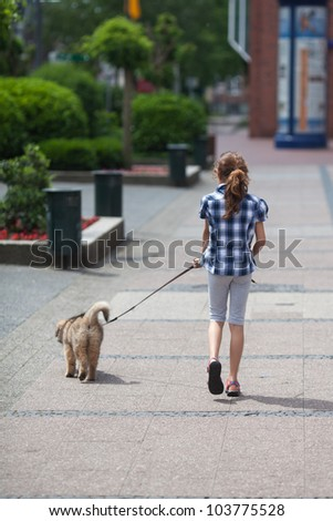 young girl walks with an Elo puppy in the city - stock photo