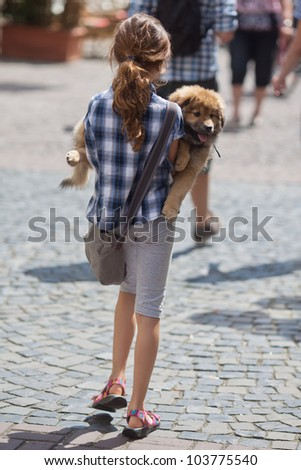 young girl walks with her puppy in the arms through the city