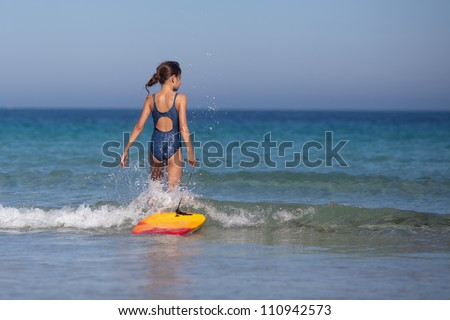 young girl walks with her surfboard in the sea