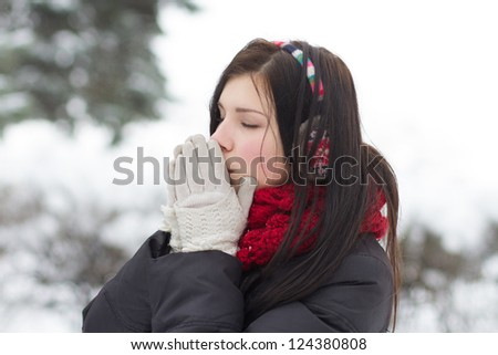 Young girl warming her frozen hands with warm breath outdoors in winter