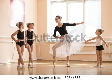 Young girl warming up and talking to younger classmates at ballet dancing class - stock photo