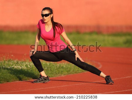 Young girl warming up on the athletism track - stock photo