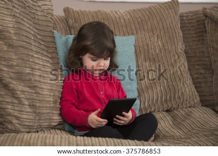 Young girl watch cartoon on Tablet