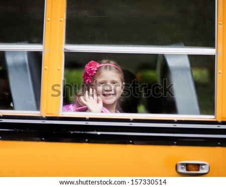 Young girl waving from school bus window - stock photo