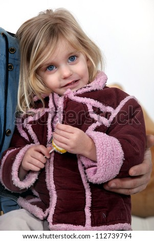 Young girl wearing a coat and holding a lolly - stock photo