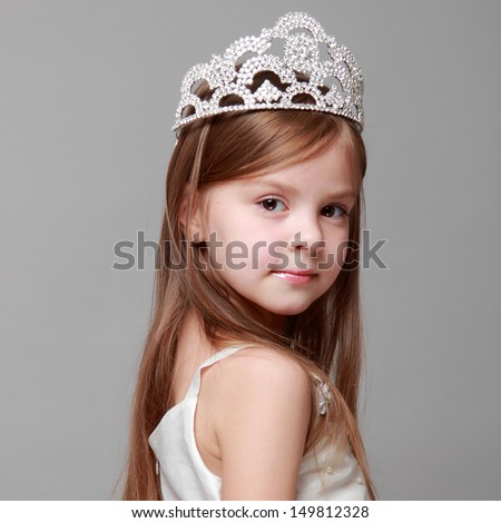 Young girl wearing a crown and a white dress with a cute smile on Holiday - stock photo