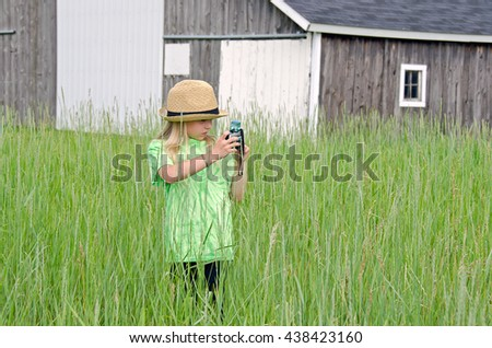 young girl wearing a fedora hat and holding old camera in rural field by wooden barn - stock photo
