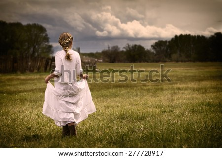 Young girl wearing a white dress walking in a pasture or prairie on a rainy cloudy day.