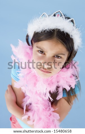 Young girl wearing crown and feather boa frowning - stock photo