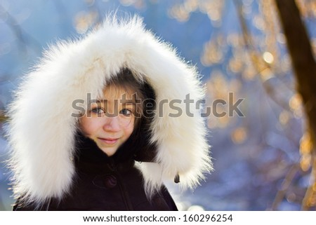 Young girl wearing fur lined coat hood - stock photo