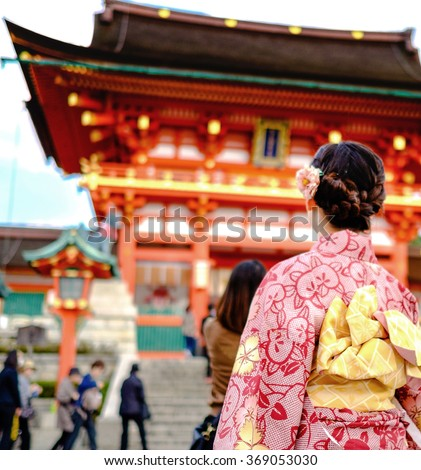 Young girl wearing Japanese kimono standing in front of japanese Temple. - stock photo