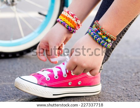 Young girl wearing loom bracelets, lacing sneakers. Young fashion, outdoors, friendship, crafts, and lifestyle concept. Bright tones. Shallow depth of field.  - stock photo