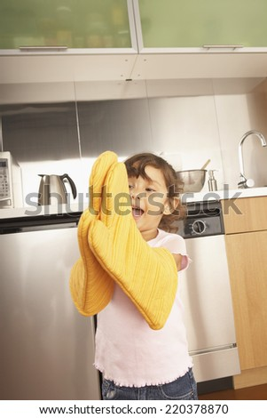 Young girl wearing oven mitts - stock photo