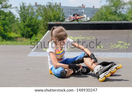 Young girl wearing rollerblades massaging her calf muscles as she sits on the ground at a skate park in front of a cement ramp