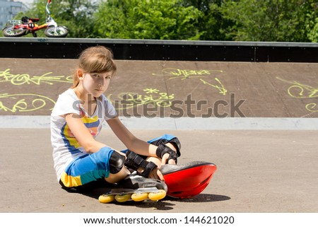 Young girl wearing rollerblades relaxing at the skate park sitting in the sun on the asphalt with her helmet resting on the ground in front of her - stock photo