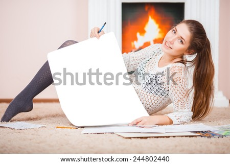 Young girl wearing white sweater with blank whatman for drawing and with colored pencils on the floor - stock photo