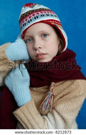 Young girl wearing woolen cap, scarf and gloves on blue