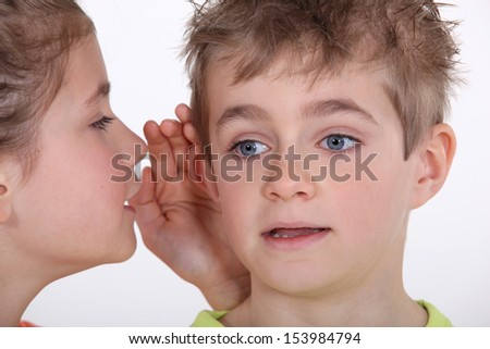 Young girl whispering into a boy's ear - stock photo