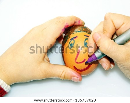 young girl who decorates an egg to kindergarten for the feast of Easter - stock photo
