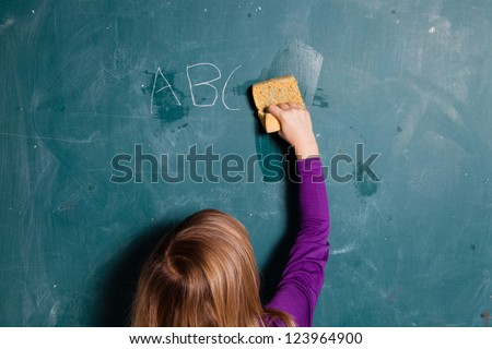 Young girl wiping letters written in chalk from chalkboard with wet sponge - stock photo