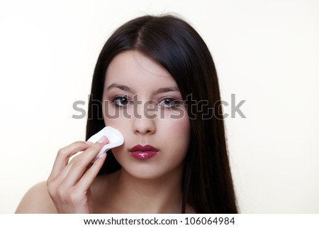 young girl wiping make up off her face