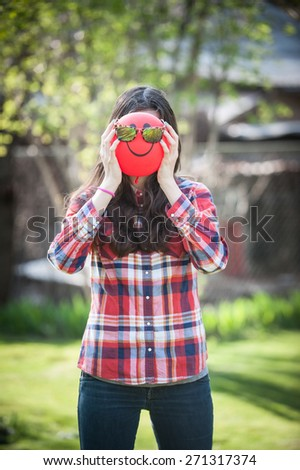 Young girl with a balloon face sunglasses on vertical - stock photo