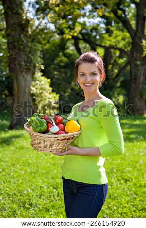 Young girl with a basket of different vegetables outdoors
