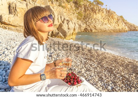 Young girl with a bob hairstyle and red lipstick eating a cherry and holding a glass in his hand on the beach