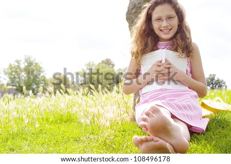 Young girl with a book in the park, smiling and looking at camera with reading glasses. - stock photo