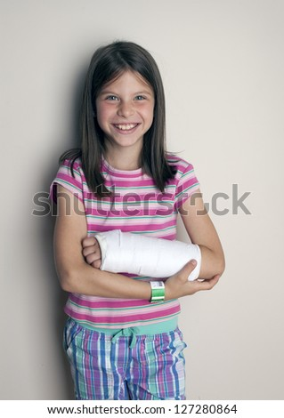 Young girl with a cast on a broken wrist or arm  smiling - stock photo