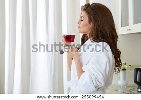 Young girl with a cup in the kitchen - stock photo