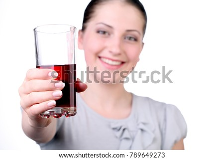 Young girl with a drink in a glass of red color