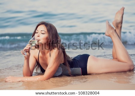 Young girl with a glass of champagne on the beach