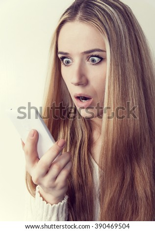 Young girl with a mobile phone receives a pleasant message. - stock photo