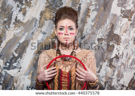 young girl with a pattern on the face and feathers looks straight into ethnic national style North American Indian background hairstyle and makeup holding a Dreamcatcher background - stock photo