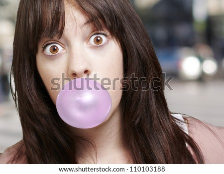 young girl with a pink bubble of chewing gum against a street background