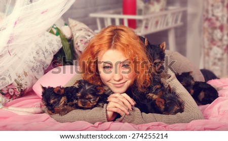 Young girl with a puppy of Yorkshire terrier. Beautiful reddish haired young woman holding a small puppy york terrier. Woman and puppy dog lying on the bed in pink room. Emotions happiness. - stock photo