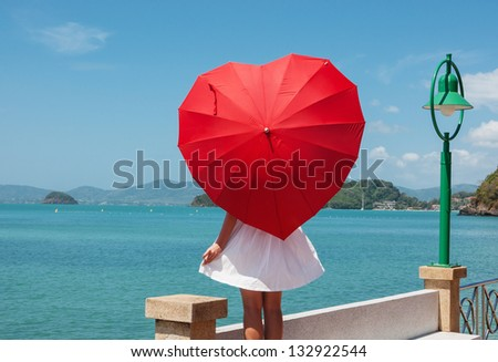 young girl with a red umbrella on the waterfront - stock photo