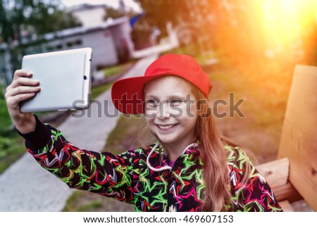 Young girl with a tablet in the park.
